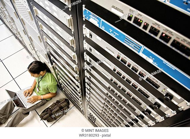 Computer technician working on a lap top computer while doing diagnostic work on a server in a larger computer server room