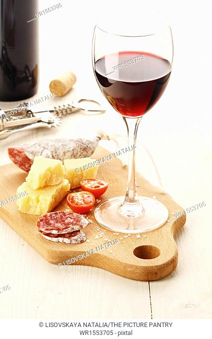 Red wine and assortment of cheese and snacks on white background