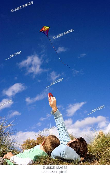 Father and son 7-9 years flying kite whilst lying on grass, rear view