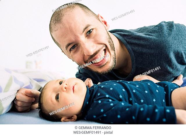 Happy father lying in bed with his newborn baby girl