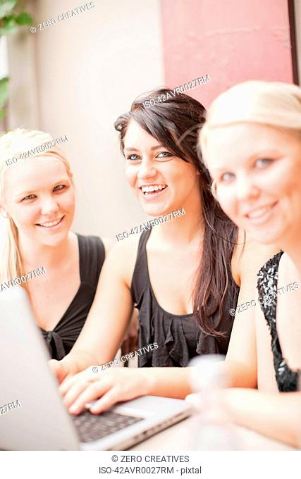 Smiling women using laptop together