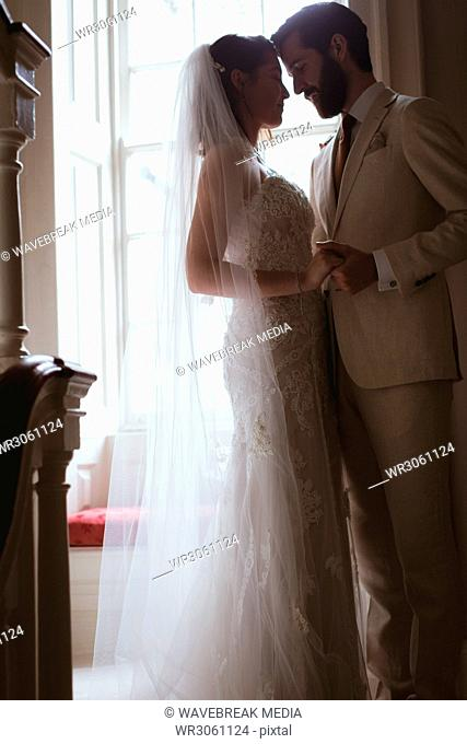 Bride and groom standing face to face on the staircase
