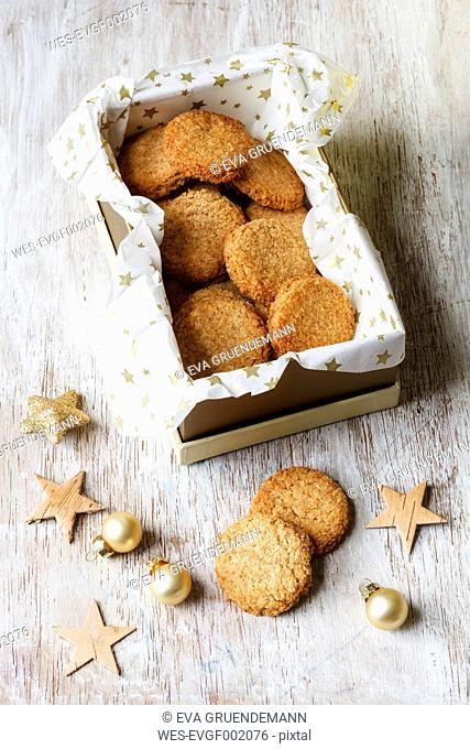 Box of whole grain cocos cookies and Christmas decoration on wood