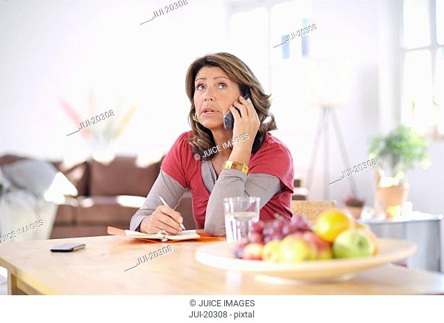 Mature woman at home on the phone