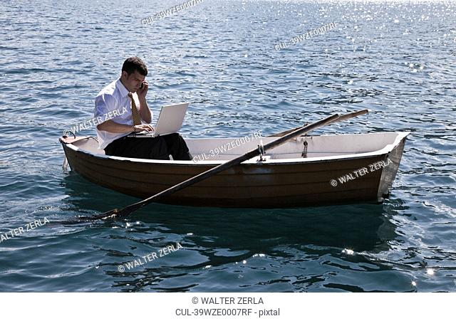 Businessman working in rowboat