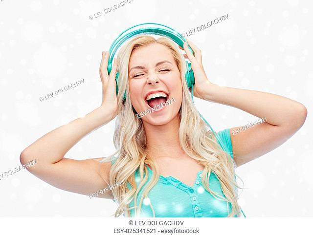 music, technology, winter holidays, christmas and people concept - happy young woman or teenage girl with headphones singing song over snow