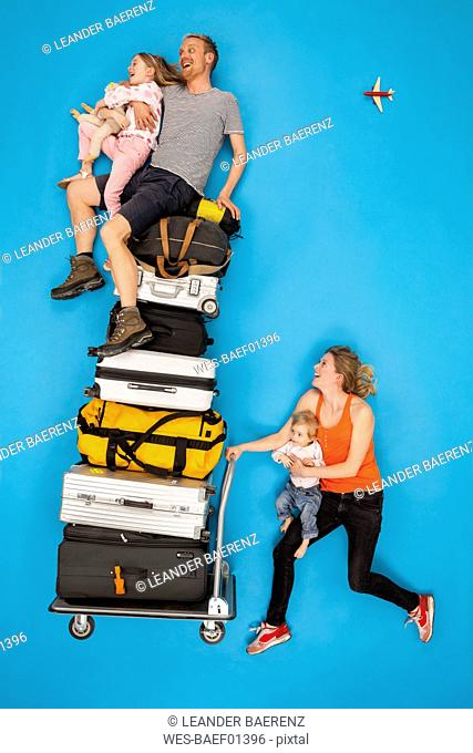 Family with luggage trolley hurrying for departure