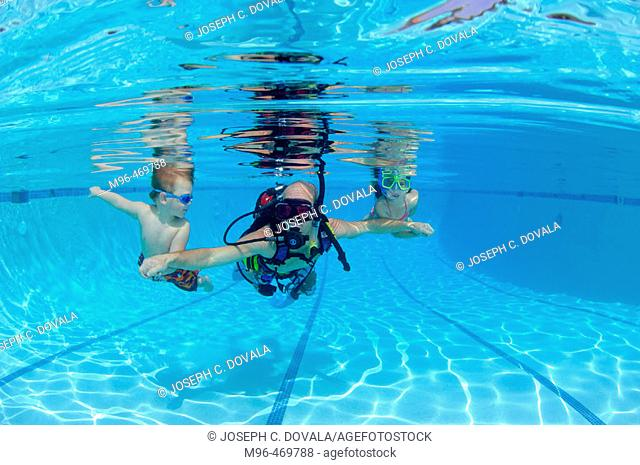 Father with son and daughter on scuba in pool