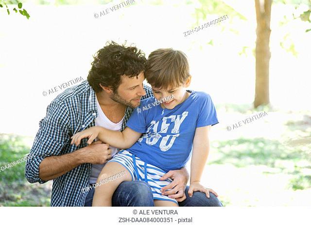 Boy sitting on father's lap