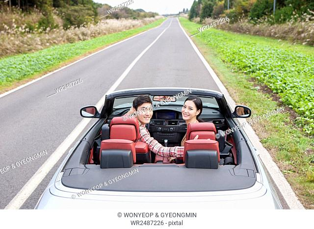 Portrait of young smiling couple travelers in a car on a road looking back