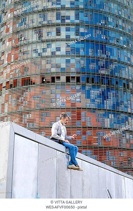 Spain, Barcelona, businessman sitting on wall using cell phone