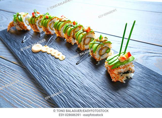 Dragon shape Sushi rice roll with nori prawn avocado sesame and teriyaki