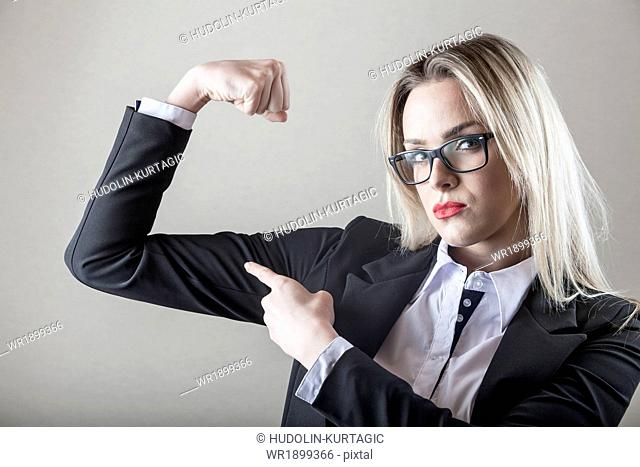 Businesswoman with eyeglasses flexing biceps