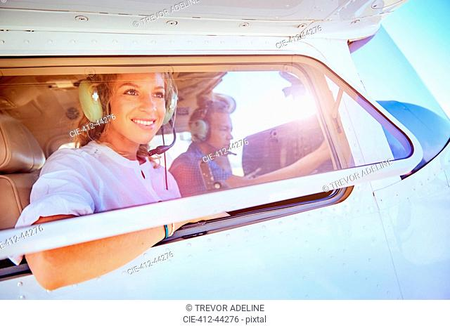 Smiling woman riding in small airplane