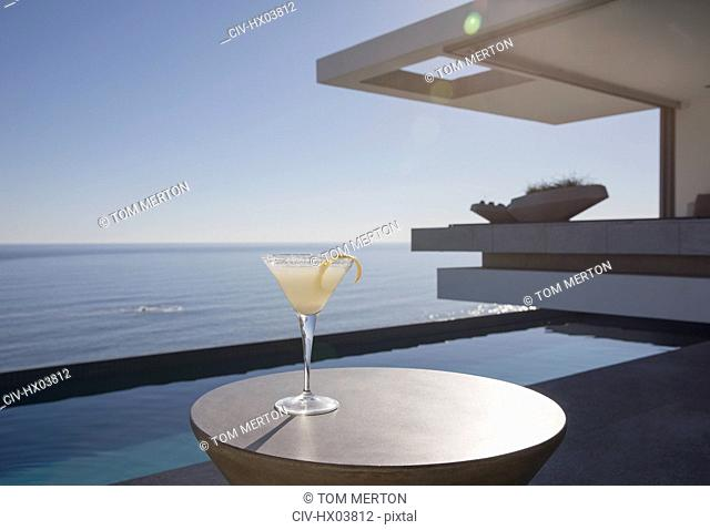 Lemon cocktail in martini glass on sunny luxury patio with ocean view