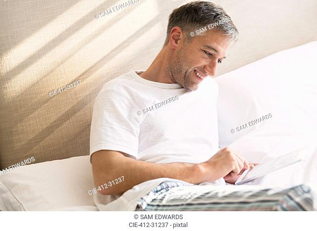 Smiling man using digital tablet in bed