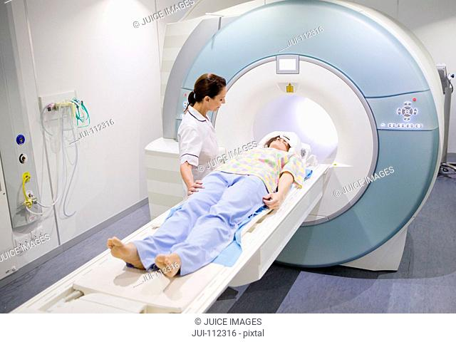 Technician nurse preparing patient for MRI scan in hospital
