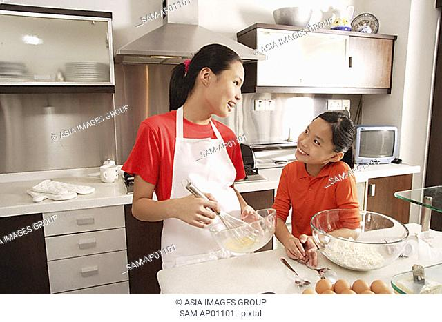 Two sisters baking in kitchen