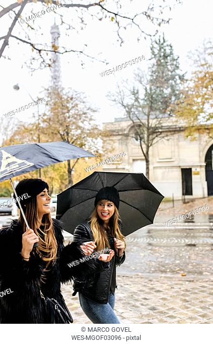 France, Paris, two young women walking in the city with the Eiffel Tower in the background