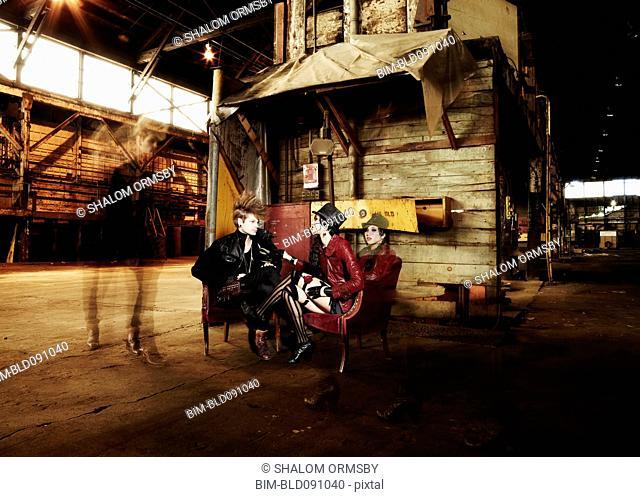 Trendy friends sitting in warehouse