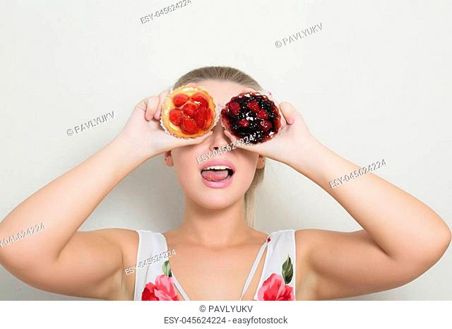 Cool blonde woman holding sweet dessert with berries and covers her eyes
