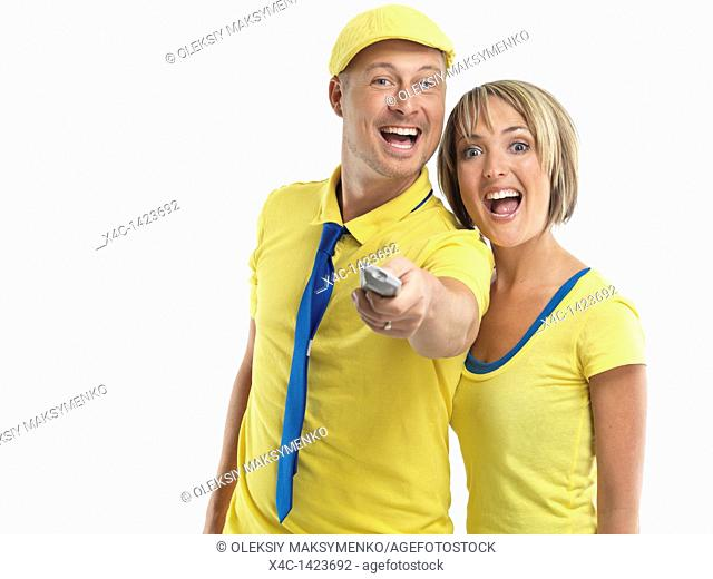 Laughing young couple with a TV remote control  Isolated on white background