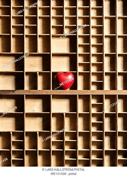 Red heart in empty wooden box with many compartments. Conceptual image of lost love, loneliness and hidden romantic feelings