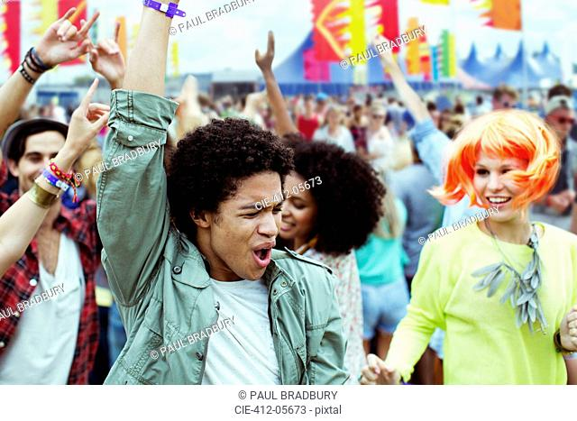 Friends dancing and cheering at music festival