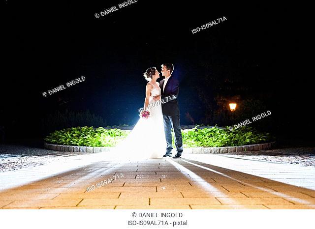 Romantic newlywed mid adult couple illuminated in garden at night