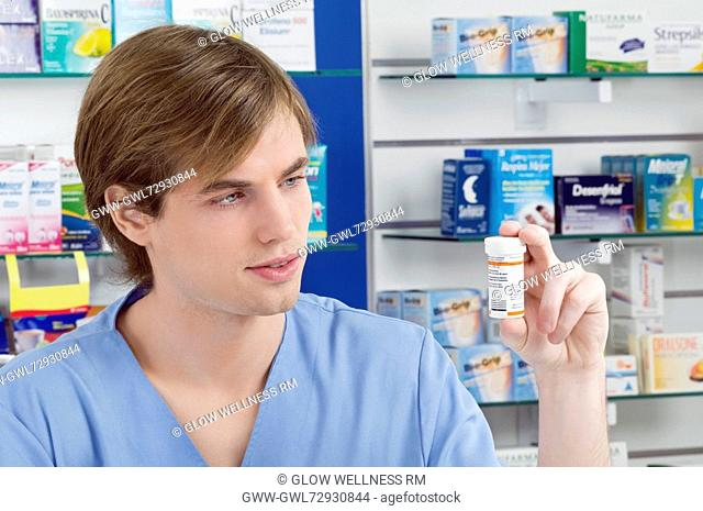 Male pharmacist holding a medicine bottle