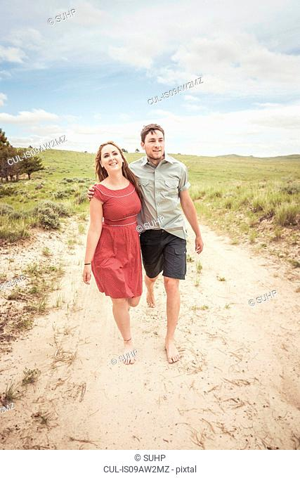 Young couple walking barefoot along sandy track, Cody, Wyoming, USA