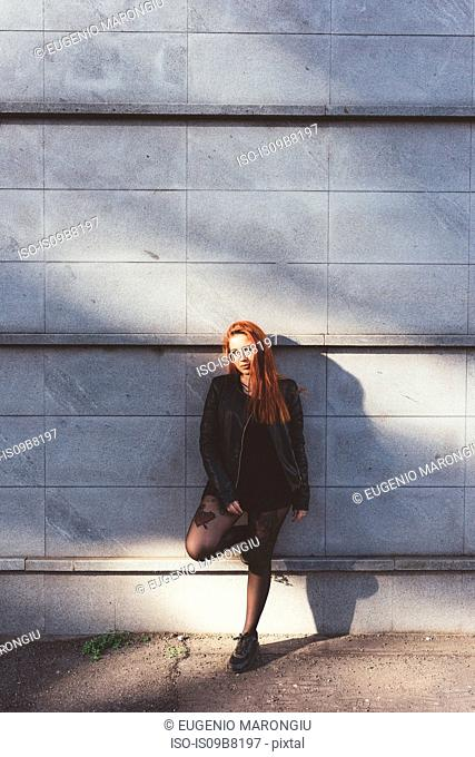 Portrait of red haired woman leaning against wall