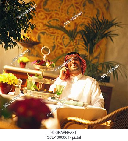 Arab businessman using cell phone at lunch break