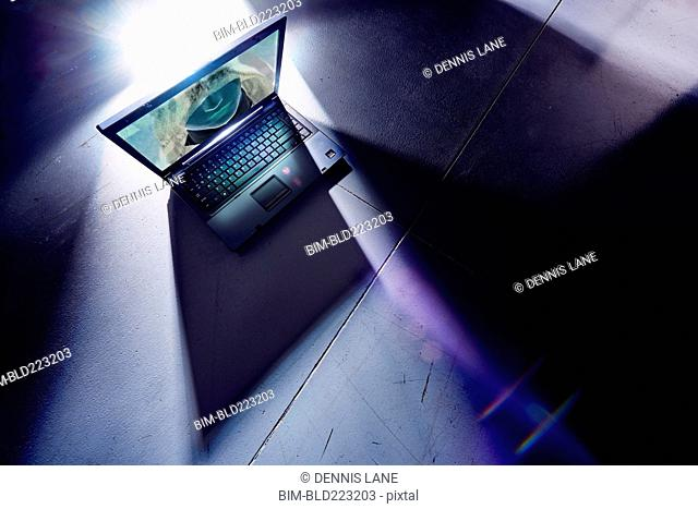 Face of hacker glowing on screen of laptop computer