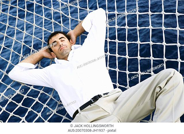 Mid adult man sleeping in the net of a ship