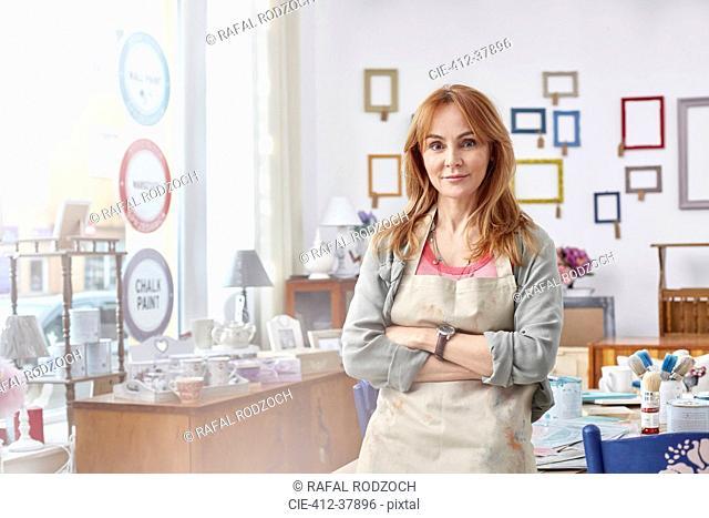 Portrait confident mature female artist painting in art studio