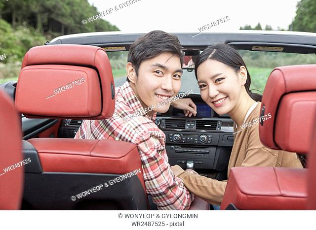Side view portrait of young smiling couple in a car looking back