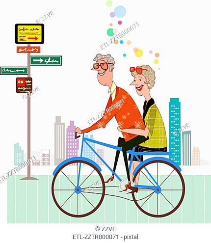 Side view of senior couple riding on bicycle