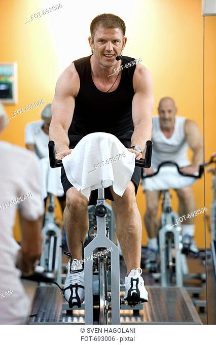 A fitness instructor on a stationary bike teaching a class