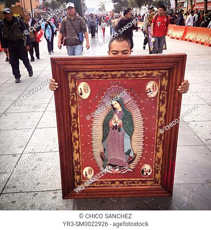 A man walks on his knees holding an image of the Virgin of Guadalupe during the annual pilgrimage to the Basilica of Our Lady of Guadalupe in Mexico City