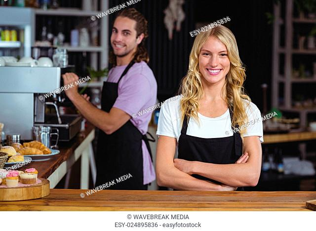 Portrait of smiling waitress standing with arms crossed at counter