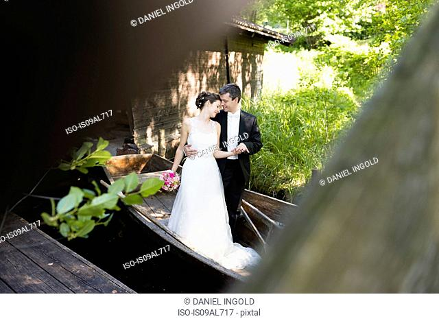 Romantic newlywed mid adult couple standing in rowing boat