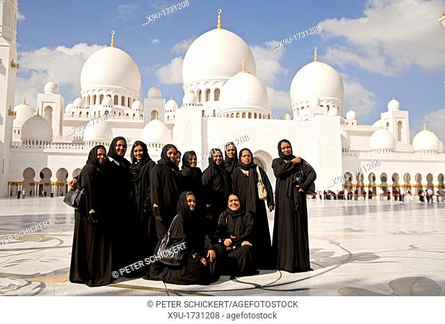 group of black veiled woman posing in front of the Sheikh Zayed Grand Mosque in Abu Dhabi, capital city of the United Arab Emirates UAE, Asia
