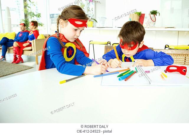 Superhero children drawing at table