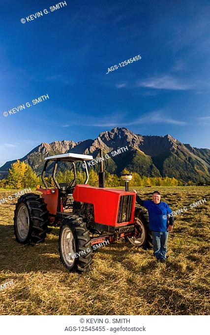 A farmer wearing a blue shirt stands next to an old red tractor in an open field, Pioneer Peak in the background, South-central Alaska; Palmer, Alaska