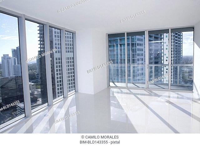 Windows of empty modern apartment overlooking cityscape