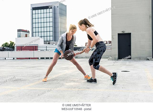 Two women playing basketball on parking level in the city