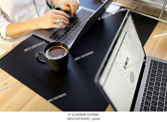 Close-up of woman using laptop at desk in office