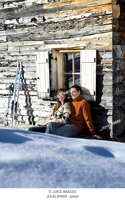 Couple sitting outside chalet in winter