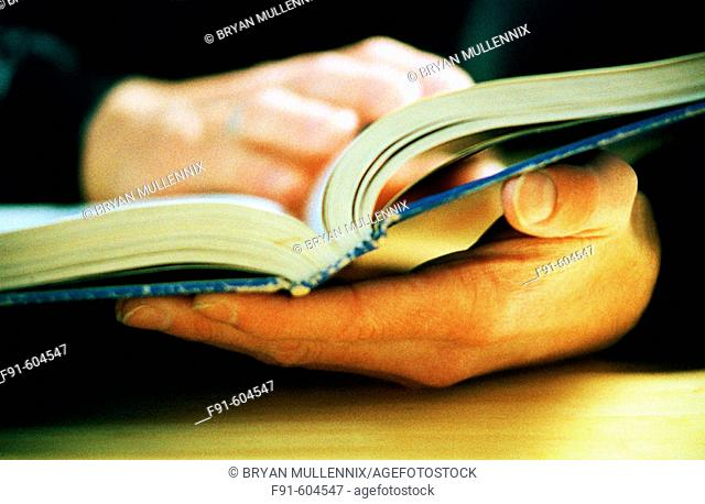 Detail of hands holding textbook